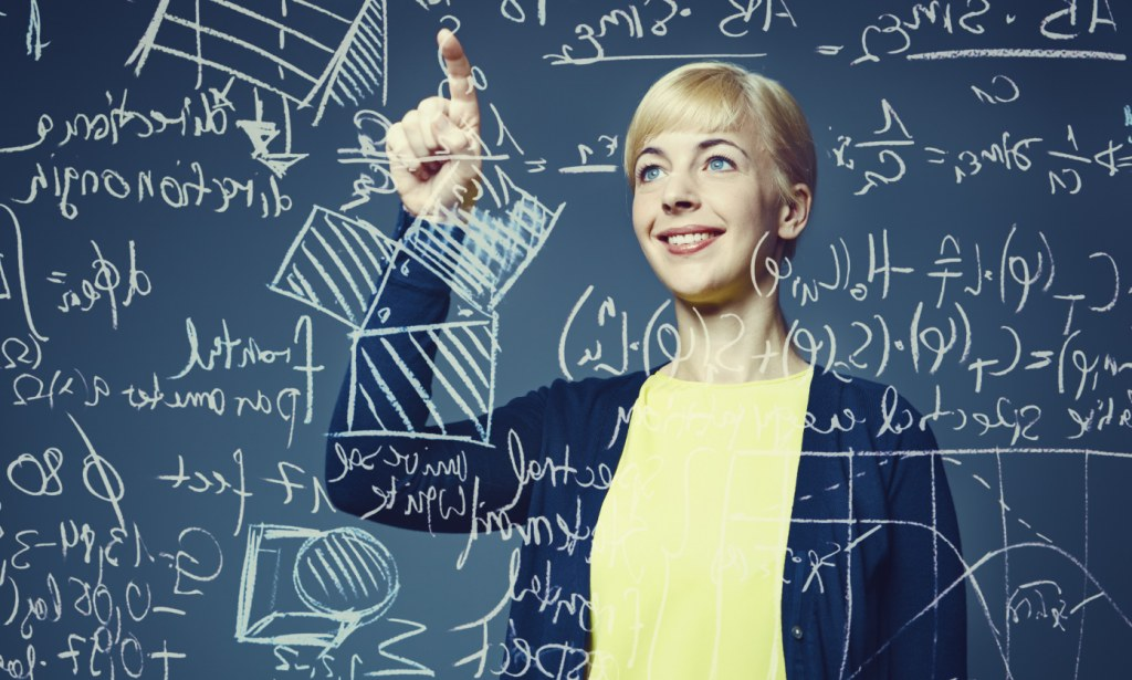 Happy young woman standing in front of glass screen with mathematical formulas written on it --- Image by © Ben Hupfer/Corbis